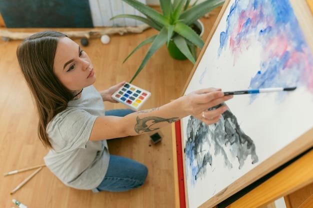Kreative zeitgenössische malerin in ihrem kunststudio