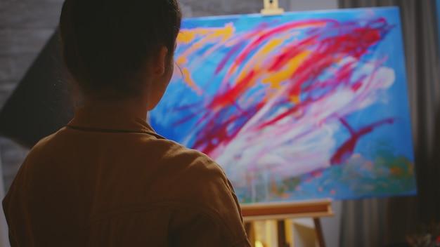 Kreative zeitgenössische malerin mit ihrer fantasie auf farbenfroher leinwand.