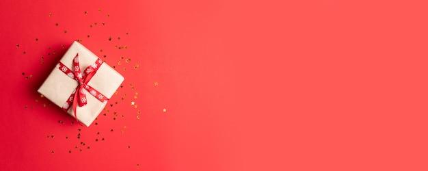 Kreative zusammensetzung der geschenkbox mit gold spielt dekoration, bälle auf rotem hintergrund die hauptrolle.