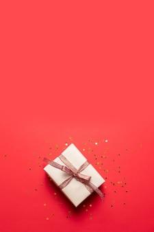 Kreative zusammensetzung der geschenkbox mit golddekorationsbogen auf rotem hintergrund. kreative flache lage, draufsichtdesign. minimales konzept des neuen jahres.