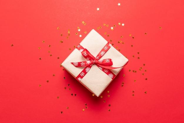 Kreative zusammensetzung der geschenkbox mit golddekorationsbogen auf rotem hintergrund. kreative flache lage, draufsichtdesign.