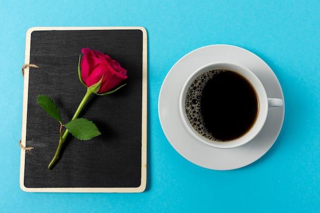Kreative zusammensetzung der roten rosenblume und der tasse kaffee auf blau.