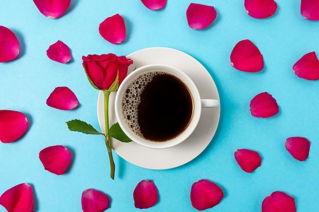 Kreative zusammensetzung der roten rosenblume und der tasse kaffee auf blauem hintergrund.