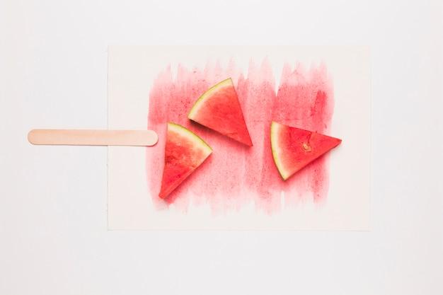 Kreative zusammensetzung des eis am stiel von der reifen wassermelone auf stock