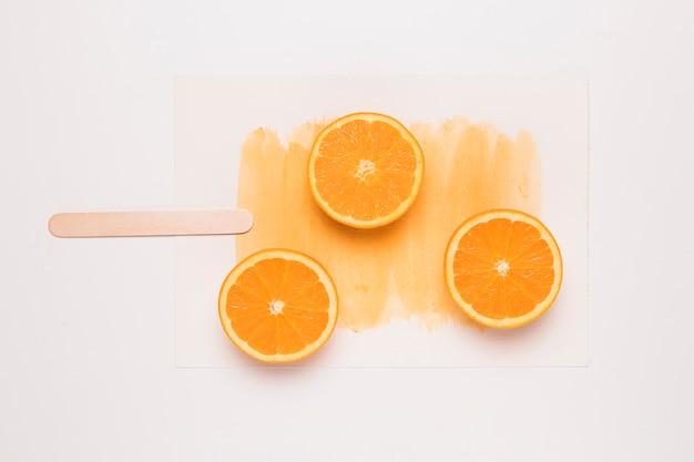 Kreative zusammensetzung des eis am stiel von geschnittener orange auf stock