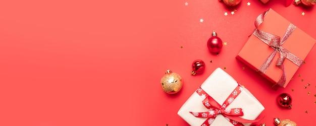 Kreative zusammensetzung mit geschenken oder geschenkkästen mit goldbögen und sternkonfettis auf roter draufsicht. flache laienzusammensetzung für geburtstag, weihnachten oder hochzeit.