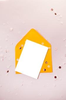 Kreative zusammensetzung mit leerem und gelbem handwerkspapierumschlag auf der schwarzen tabelle obenliegend für heiratsebenenlage