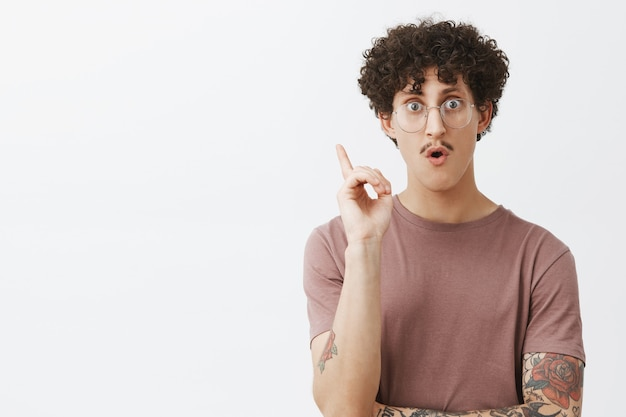 Kreativer ad kluger junger mann mit dem lockigen dunklen haar des schnurrbartes und dem tätowierten arm, der zeigefinger in eureka-geste hebt, keuchend herausfindet große idee heraus oder erfindet genialen plan, der vorschlag hinzufügt
