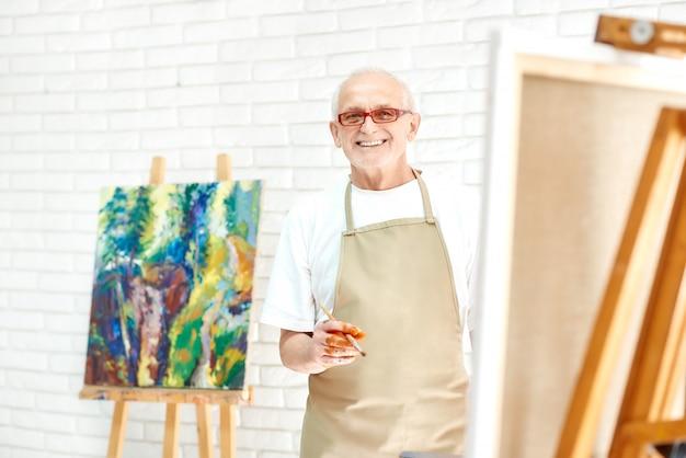 Kreativer älterer maler, der bunte abstrakte malerei am hellen studio zeichnet.