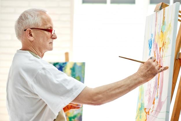 Kreativer älterer maler, der buntes bild am hellen studio zeichnet.
