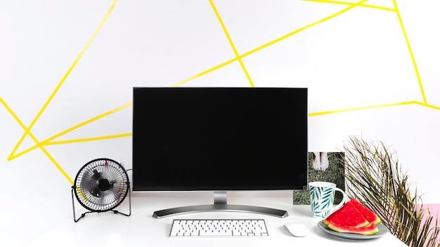 Kreativer arbeitsplatz des sommers mit leerem bildschirm