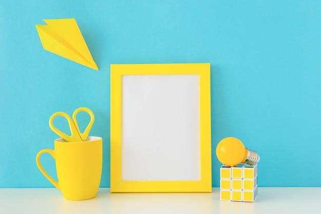 Kreativer arbeitsplatz in den blauen und gelben farben mit rubiks würfel und birne