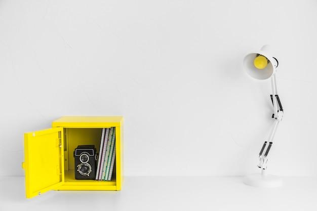 Kreativer arbeitsplatz in den weißen und gelben farben mit kasten und alter kamera