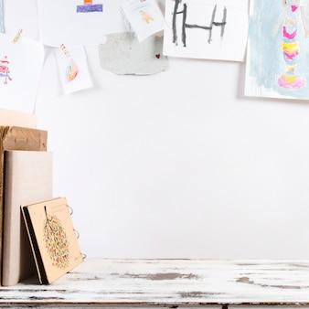 Kreativer arbeitsplatz mit den zeichnungen des kindes auf wand