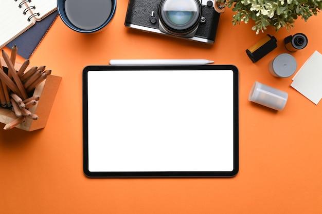 Kreativer arbeitsplatz mit digitalem tablet, kamera, kaffeetasse und notebook auf orangem hintergrund.