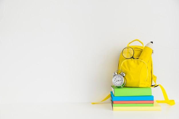 Kreativer arbeitsplatz mit gelbem rucksack und notizbüchern