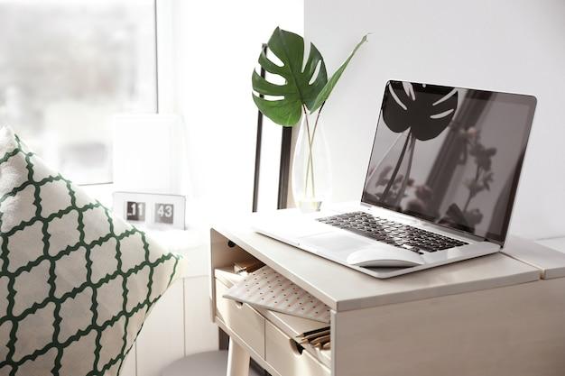 Kreativer arbeitsplatz mit laptop nahe fensterbank im modernen raum