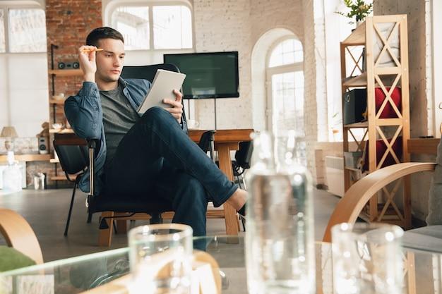 Kreativer arbeitsplatz - organisierter arbeitsplatz nach belieben zur inspiration. mann, der im büro in bequemer kleidung, entspannter position und unordentlichem tisch arbeitet. wählen sie die gewünschte atmosphäre - ideal klar oder chaos.