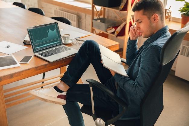 Kreativer arbeitsplatz – organisierter arbeitsplatz nach belieben zur inspiration mann, der im büro in bequemer kleidung, entspannter position und unordentlichem tisch arbeitet. wählen sie die gewünschte atmosphäre - ideal klar oder chaos.