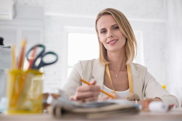 Kreativer beruf. niedriger winkel des angenehmen weiblichen couturiers, der kamera während des skizzierens anstarrt