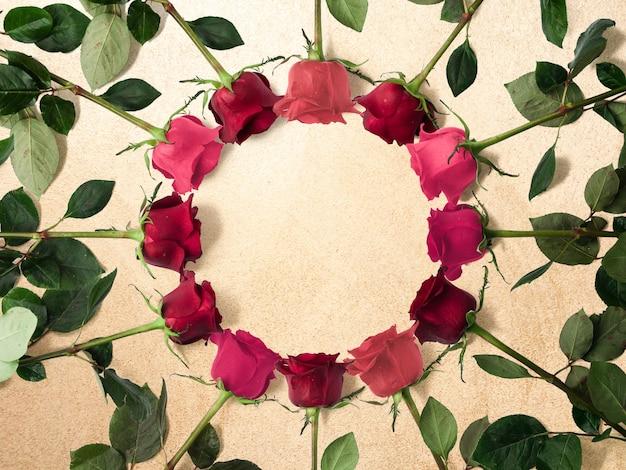 Kreativer blumenrahmen aus rosen auf goldenem sand mit kopierraum, flacher lage, draufsicht
