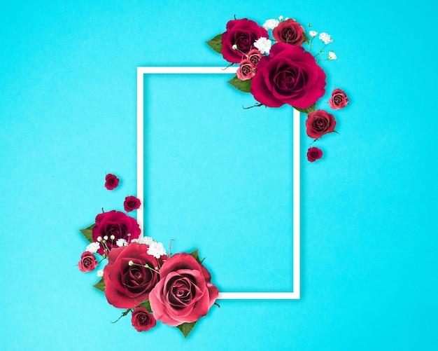 Kreativer blumenrahmen aus rosen mit kopienraum auf blauem hintergrund, blumenhintergrund, glücklicher valentinstag, muttertag, flache lage, draufsicht