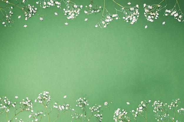Kreativer blumenrahmen aus weißen dekorativen blumen auf grünem hintergrund mit kopienraum