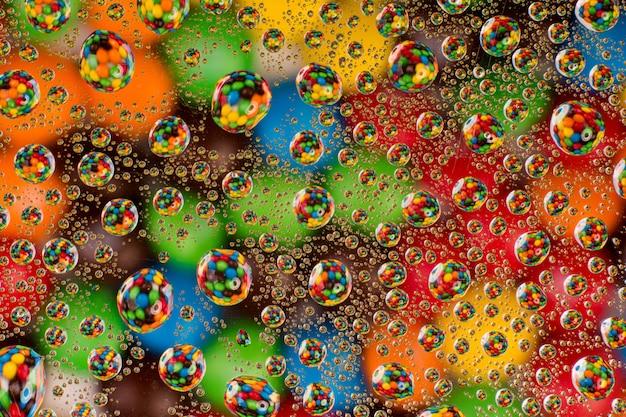 Kreativer bunter hintergrund. bunte süßigkeit durch wassertropfen auf glas
