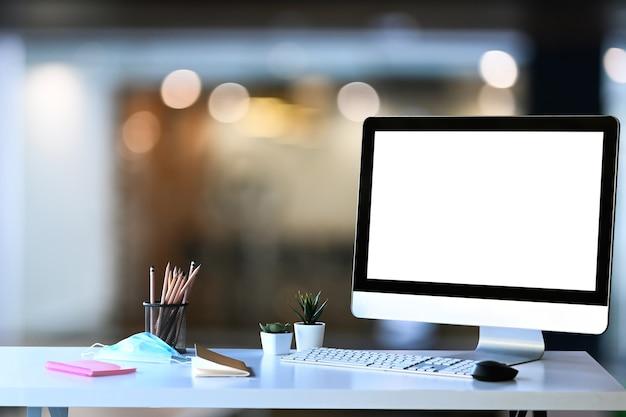 Kreativer designer-arbeitsplatz mit computer, papierkram, schreibwaren und schutzmaske auf weißem tisch.