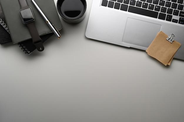 Kreativer designer-arbeitsplatz mit laptop-computer, smartwatch, notizbuch und kopienraum auf weißem tisch.