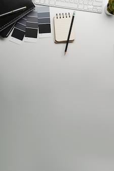 Kreativer designer-arbeitsplatz mit notizbuch, farbfeldern, tastatur und kopienraum auf weißem hintergrund
