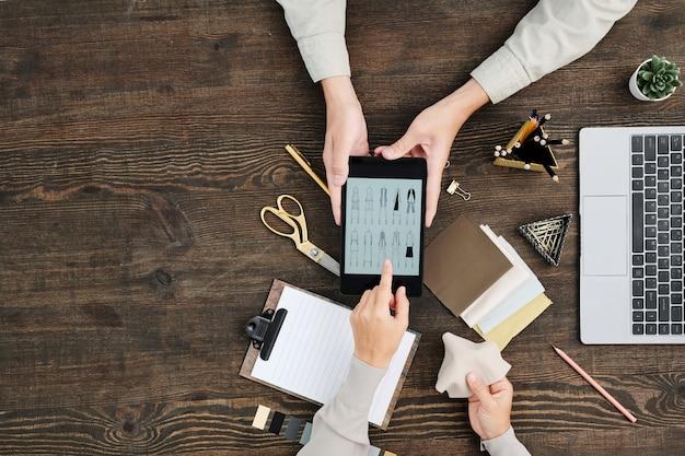 Kreativer designer des flachen layings der hände, der auf skizzen auf anzeige des tabletts zeigt, das vom kollegen über holztisch mit textilproben gehalten wird
