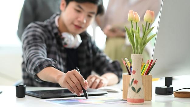 Kreativer designer des jungen mannes, der an digitalem tablet im modernen büro arbeitet.