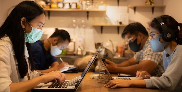 Kreativer designer-geschäftsarbeiter, der in abständen arbeitet und eine medizinische gesichtsmaske trägt um die ausbreitung des coronavirus covid-2019 zu verhindern, kann das home office für kleine personengruppen von zu hause aus arbeiten