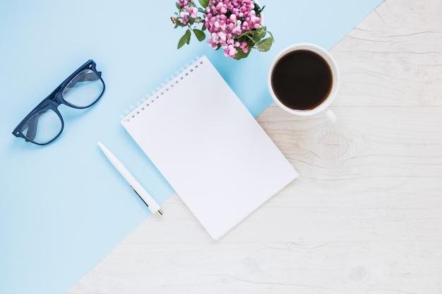 Kreativer desktop mit notizbuch und kaffee
