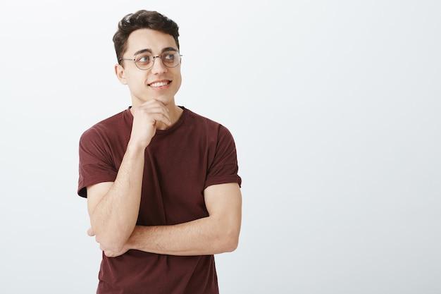Kreativer erfolgreicher europäischer geschäftsmann im roten t-shirt und in der runden trendigen brille