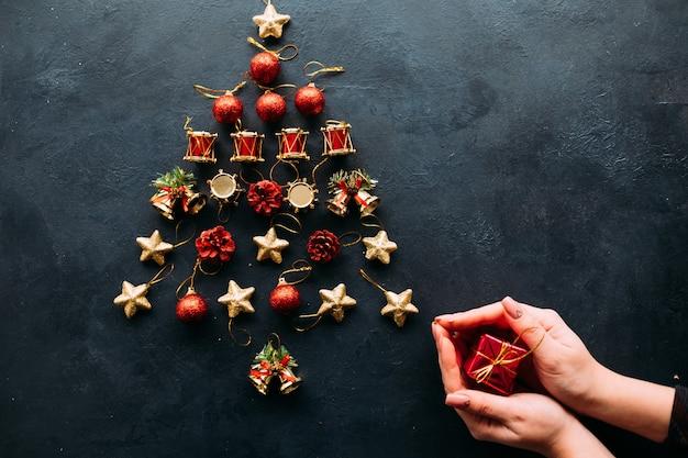 Kreativer feiertag des weihnachtsspielzeugsortimentbaums auf dunkler wand. Premium Fotos