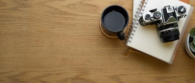 Kreativer flacharbeitsbereich mit notizbüchern, kamera, kaffeetasse und kopierbereich im arbeitszimmer