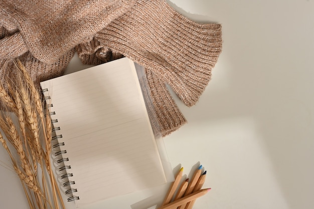 Kreativer flacher arbeitsbereich mit notizbuch, buntstiften, pullover und weizen, dekoriert auf dem tisch, draufsicht