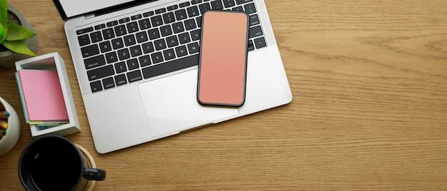 Kreativer flacher arbeitsbereich mit smartphone, laptop, kaffeetasse und schreibwaren im arbeitszimmer