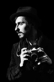Kreativer fotograf, der im studio mit kamera aufwirft
