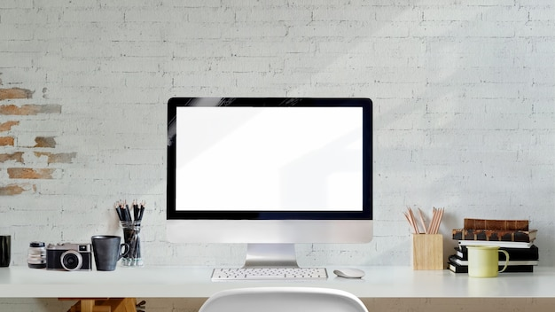 Kreativer fotografarbeitsplatz des dachbodens mit computer des leeren bildschirms auf weißem hölzernem schreibtisch.