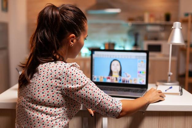 Kreativer freiberufler, der nachts bilder im home-office auf dem notebook retuschiert. fotograf, der postproduktion mit software und performance-laptop, künstler, beruf, bildschirm, grafik durchführt