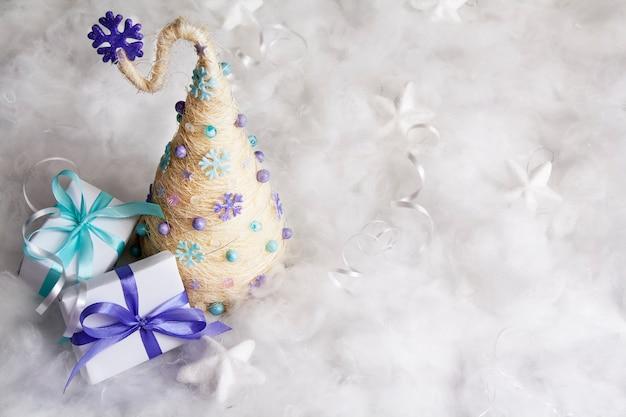 Kreativer fröhlicher weihnachtsbaum mit geschenken im schnee mit kopienraum. fröhliche weihnachten