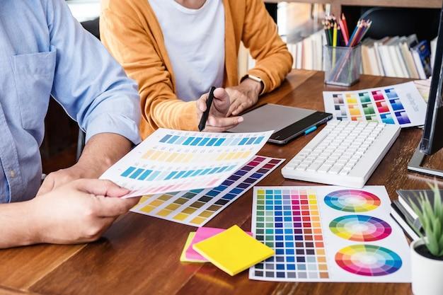 Kreativer grafikdesigner mit zwei kollegen, der an farbauswahl arbeitet und auf grafiktablett zeichnet