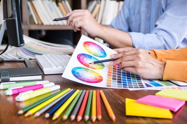 Kreativer grafikdesigner mit zwei kollegen, der an farbauswahl arbeitet und auf grafiktablette am arbeitsplatz zeichnet