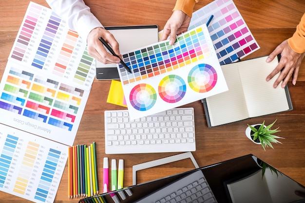 Kreativer grafikdesigner mit zwei kollegen, der an farbauswahl und farbmustern arbeitet und zeichnen auf grafiktablette
