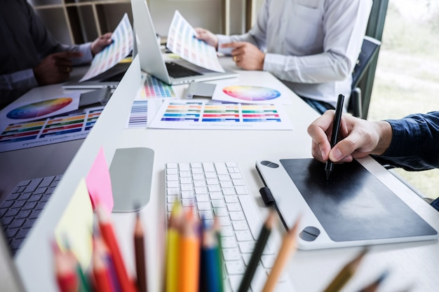 Kreativer grafikdesigner mit zwei kollegen, der an farbauswahl und farbmustern arbeitet