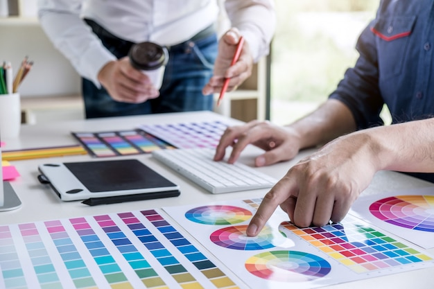 Kreativer grafikdesigner mit zwei kollegen, der an farbauswahl und -zeichnung arbeitet