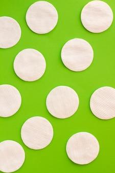 Kreativer grüner hintergrund von weißen baumwollauflagen für hautpflege.
